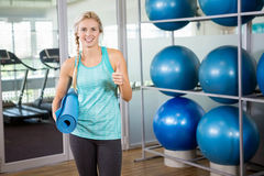 Fit blonde holding mat and showing thumb up Stock Photo
