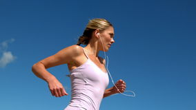 Fit blonde jogging and listening to music on sunny day stock video