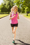 Fit blonde jogging in the park Royalty Free Stock Photos