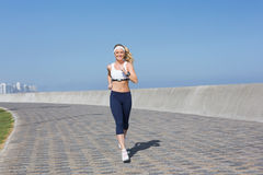 Fit blonde jogging on the pier Royalty Free Stock Photography