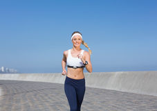 Fit blonde jogging on the pier Stock Photo