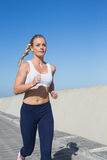 Fit blonde jogging on the pier Royalty Free Stock Image
