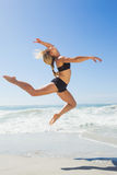Fit blonde jumping gracefully on the beach Royalty Free Stock Images