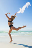 Fit blonde jumping gracefully with scarf on the beach Royalty Free Stock Photo