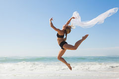 Fit blonde jumping gracefully with scarf on the beach Royalty Free Stock Image