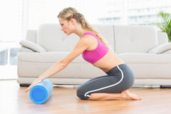 Fit blonde kneeling on floor using foam roller Royalty Free Stock Photography