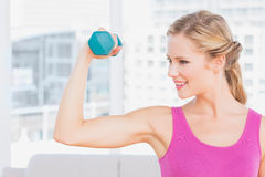 Fit blonde lifting dumbbell and flexing Royalty Free Stock Photography