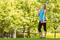 Fit blonde lifting dumbbells in the park Stock Photography