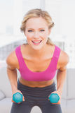 Fit blonde lifting dumbbells and smiling at camera Stock Image
