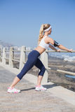 Fit blonde listening to music warming up Royalty Free Stock Photography