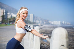 Fit blonde listening to music warming up Stock Photo