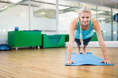 Fit blonde planking on mat. In fitness studio stock images