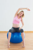 Fit blonde pregnant woman sitting on exercise ball Stock Photo