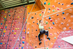 Fit blonde rock climbing indoors Royalty Free Stock Photos