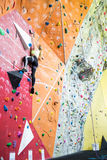 Fit blonde rock climbing indoors Royalty Free Stock Photography