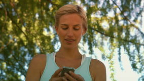 Fit blonde sending a text in the park stock video