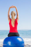 Fit blonde sitting on exercise ball looking at sea Royalty Free Stock Photography