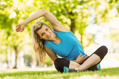 Fit blonde sitting on the grass Royalty Free Stock Photos