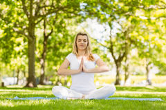 Fit blonde sitting in lotus pose in the park Royalty Free Stock Image