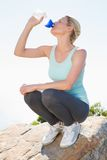 Fit blonde sitting at summit drinking from water bottle Stock Photo