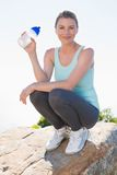 Fit blonde sitting at summit holding water bottle smiling at camera Royalty Free Stock Photography
