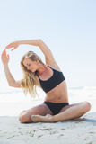 Fit blonde sitting in yoga pose on the beach Stock Image
