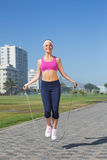 Fit blonde skipping rope on the pier Royalty Free Stock Photo