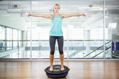 Fit blonde standing on bosu ball and lifting dumbbells. In fitness studio Royalty Free Stock Photo