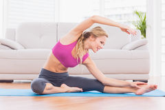 Fit blonde stretching on exercise mat Royalty Free Stock Images