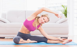 Fit blonde stretching on exercise mat smiling at camera Royalty Free Stock Images