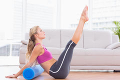 Fit blonde stretching on floor using foam roller Royalty Free Stock Image