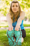 Fit blonde stretching on the grass Stock Image