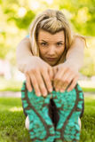 Fit blonde stretching on the grass Royalty Free Stock Photos
