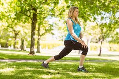 Fit blonde stretching on the grass Stock Photo
