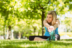 Fit blonde stretching on the grass Stock Images