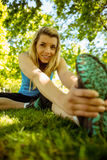 Fit blonde stretching on the grass Royalty Free Stock Photo