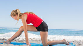 Fit blonde stretching leg on exercise mat Stock Photo