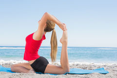 Fit blonde stretching leg in yoga pose. On the beach Royalty Free Stock Photography