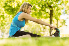 Fit blonde stretching in the park Royalty Free Stock Photography