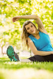 Fit blonde stretching in the park Royalty Free Stock Images