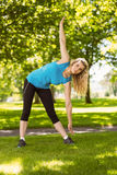 Fit blonde stretching in the park Royalty Free Stock Photos