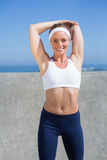 Fit blonde stretching on the pier. On a sunny day Stock Photos