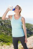 Fit blonde taking a break at summit drinking water Royalty Free Stock Photography