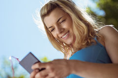 Fit blonde texting on her smartphone Royalty Free Stock Images