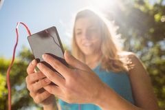 Fit blonde texting on her smartphone Stock Photography