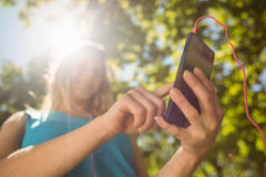 Fit blonde texting on her smartphone Stock Image