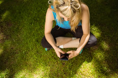 Fit blonde texting on her smartphone Royalty Free Stock Image