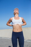 Fit blonde touching her back on the pier. On a sunny day Royalty Free Stock Photography