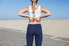 Fit blonde touching her back on the pier. On a sunny day Stock Photo