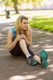 Fit blonde touching her injured knee on path Royalty Free Stock Photo